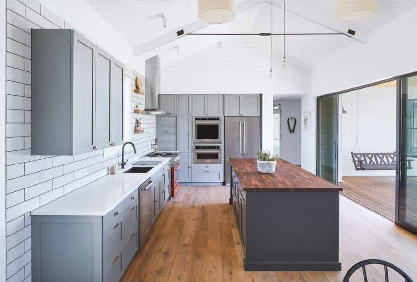 This Scandinavian-Style kitchen has a white cathedral ceiling that is paired with white-tiled walls with a brick wall design. This makes the gray tones of the kitchen island and kitchen peninsula to pop out as well as the wooden countertop.
