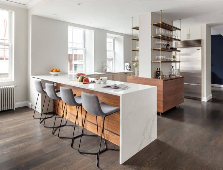 The elegant design of the kitchen island with built-in golden shelves is an amazing concept. This is surrounded by an L-shaped peninsula that has white countertops that contrast the dark wooden floors of this Scandinavian-Style kitchen.