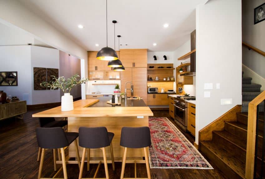 The dark tones of the hardwood flooring are topped by a worn patterned area rug that separates the cooking area and the kitchen island that has an L-shaped bar paired with dark gray stools. The far wall is dominated by a large wooden structure of cabinets and shelves.