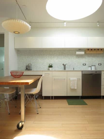 The white ceiling is dominated by a large circular sunroof that illuminates the hardwood floor. The flooring matches with the wooden table that is attached to the kitchen peninsula. The peninsula has white built-in cabinets that house the dishwasher.