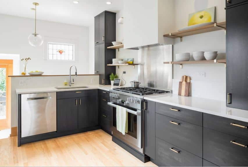 The white walls and white ceiling of this Scandinavian-Style kitchen are contrasted by elegant dark gray built-in cabinets and drawers. The L-shaped peninsula supports these cabinets and drawers and contrasts them with a white countertop.