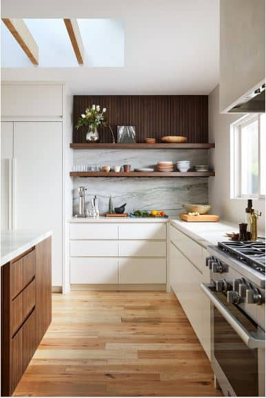 The white fridge is beside a wall that has wooden slats at the top and marble backsplash with wooden shelves. This backsplash extends to the countertop of the L-shaped peninsula that has white cabinets and drawers as opposed to the kitchen island's dark wooden elements.