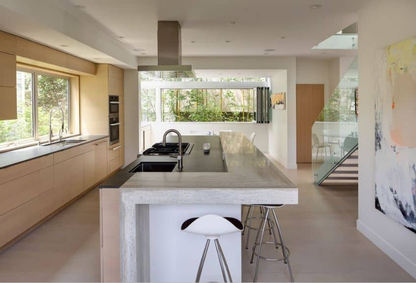 This airy kitchen has a central kitchen island fitted with an L-shaped bar paired with modern metallic stools that match well with the modern appliances. Across from the kitchen island is a wide window that illuminates the kitchen peninsula's sink area.