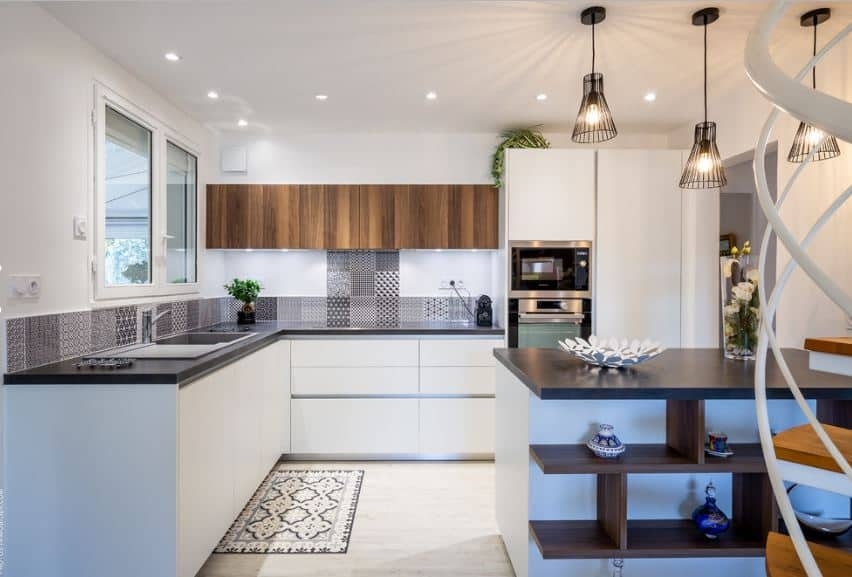 This Scandinavian-Style kitchen has lovely patterned tiles for its backsplash that contrasts the white walls and complements the dark countertop of the L-shaped peninsula. The white flooring that blends well with the white cabinets and drawers is topped by a patterned area rug.