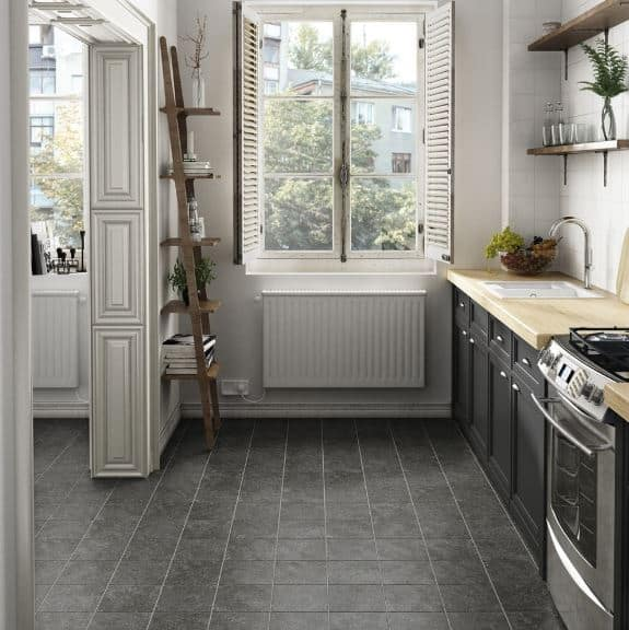 The dark-tiled flooring blends well with the drawers and cabinets of the kitchen peninsula that has a wooden countertop. The charming ladder shelf by the shuttered windows pairs with the floating shelves mounted on the white-tiled wall.