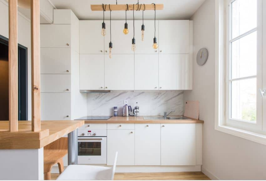 A large white wooden structure dominates the wall of this Scandinavian-Style kitchen with built-in cabinets that extend to the small kitchen peninsula housing a small oven and sink. These are all brightened up by the large window that brings in natural light.