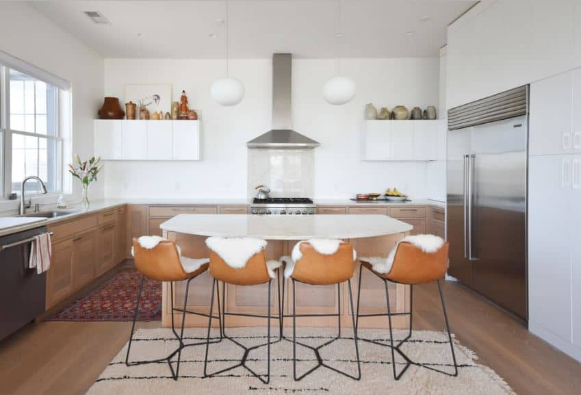 The modern stools facing the kitchen island is cushioned with white furs that go well with the white countertops and walls of the kitchen. The cooking area is flanked by two spherical pendant lights hanging from the white ceiling.