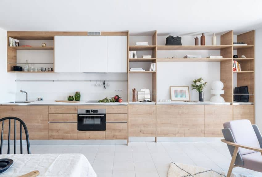 The wooden structure built into the white wall of this Scandinavian-Style kitchen has built-in cabinets and shelves that extend all the way to the living room's shelves and cabinets. The white-tiled flooring mirrors the white ceiling that gives the wooden elements emphasis.