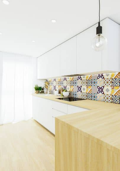 This Scandinavian-Style kitchen is given a bit of Spanish-Style flair with colorful patterned tiles filling the wall between the hanging white cabinets and the L-shaped kitchen peninsula that has wooden countertops that extend to the hardwood floors.