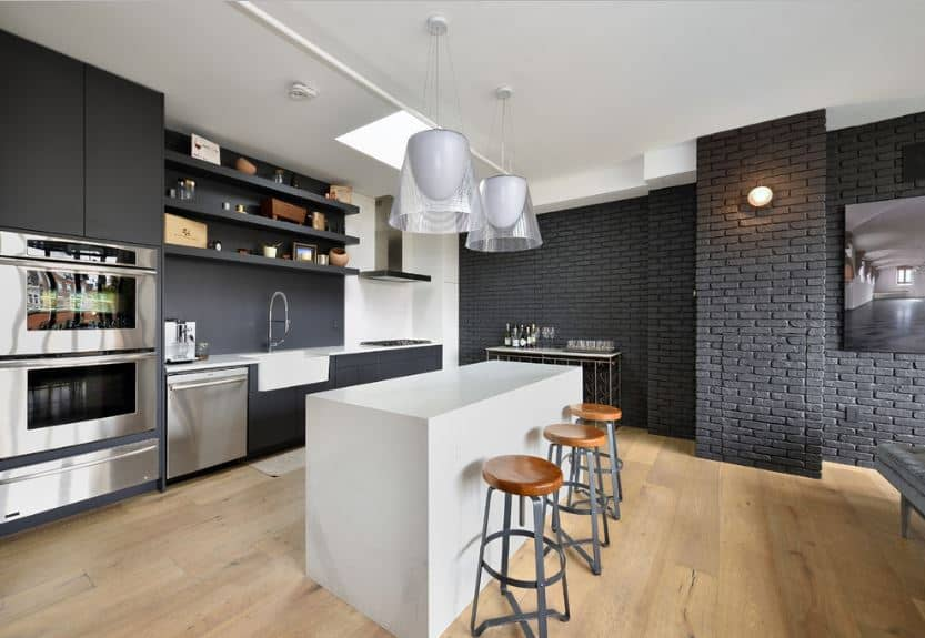 A pair of modern white pendant lights hang over the pure white kitchen island that looks like a big block of white wood. Contrasting this are two dark-toned walls. One is a textured brick wall painted with dark gray and the other is dominated by a wooden structure housing the oven, dishwasher, sink and stove.