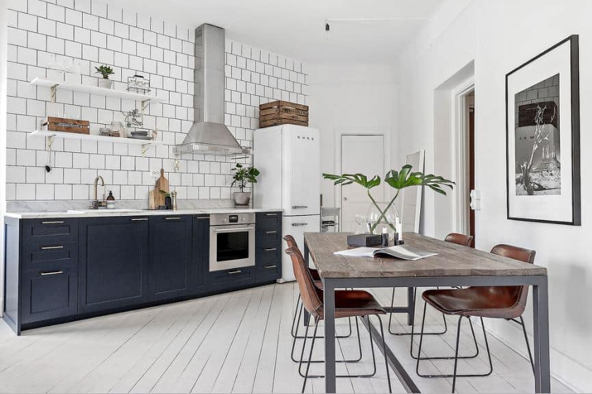 This is a simple Scandinavian-Style kitchen with a small navy blue kitchen peninsula against a white wall that has white tiles arranged in a brick wall pattern. This pairs well with the white wooden flooring and a white ceiling that is shared with the dining area.