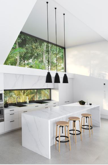 The high white ceiling of this Scandinavian-Style kitchen is augmented by massive windows that offer a lush green scenery outside. This contrasts the white walls and marble white kitchen island topped with a trio of modern pendant lights.