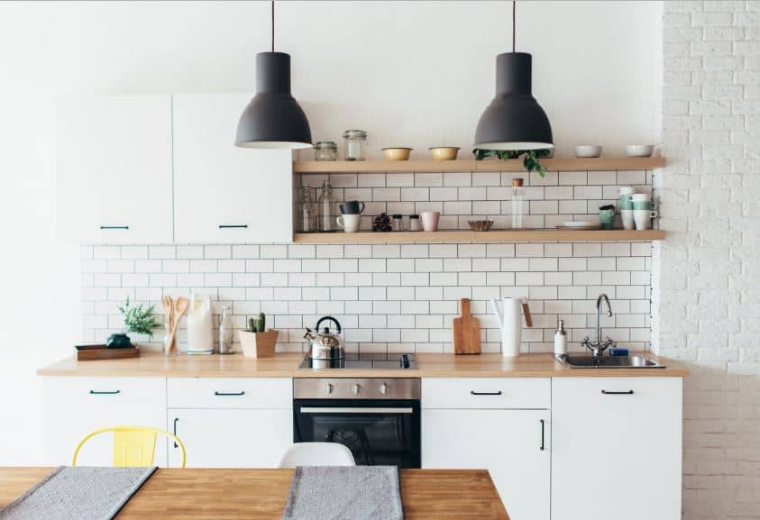 The hanging cabinets seem to blend into the white walls. This is attached to a couple of hanging wooden shelves over the kitchen peninsula against the tiled wall. It has a countertop with the same wooden hue as the shelves.