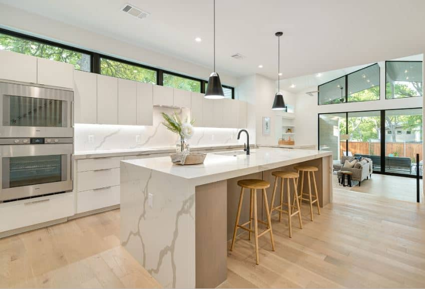 The pair of hanging pendant lights over the marble kitchen island is augmented by the backlight underneath the white wall-mounted cabinets over the kitchen peninsula. The brightness is complemented by the white walls and hardwood flooring.