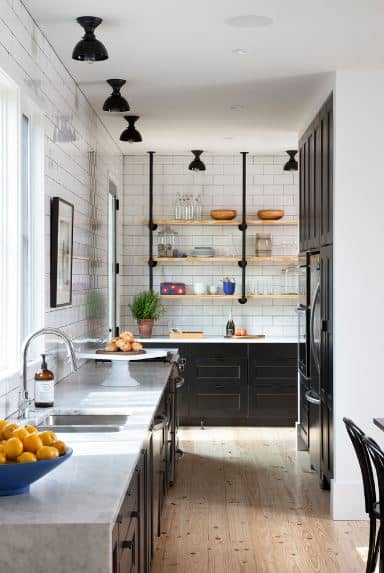 The sleek white-tiled walls match well with the marble countertop of the L-shaped peninsula. This is contrasted with dark wooden built-in cabinets and drawers that match the ceiling-mounted lights that look like dark goblets.