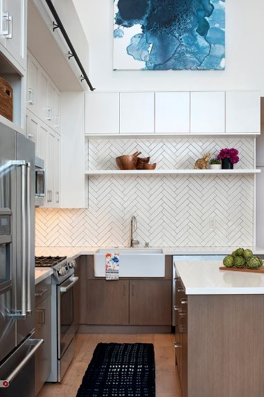 There is a beautiful bluish painting mounted over the hanging white cabinets that extend to the wooden structure housing the microwave oven over the cooking area of the U-shaped peninsula with white countertops and dark wooden drawers.