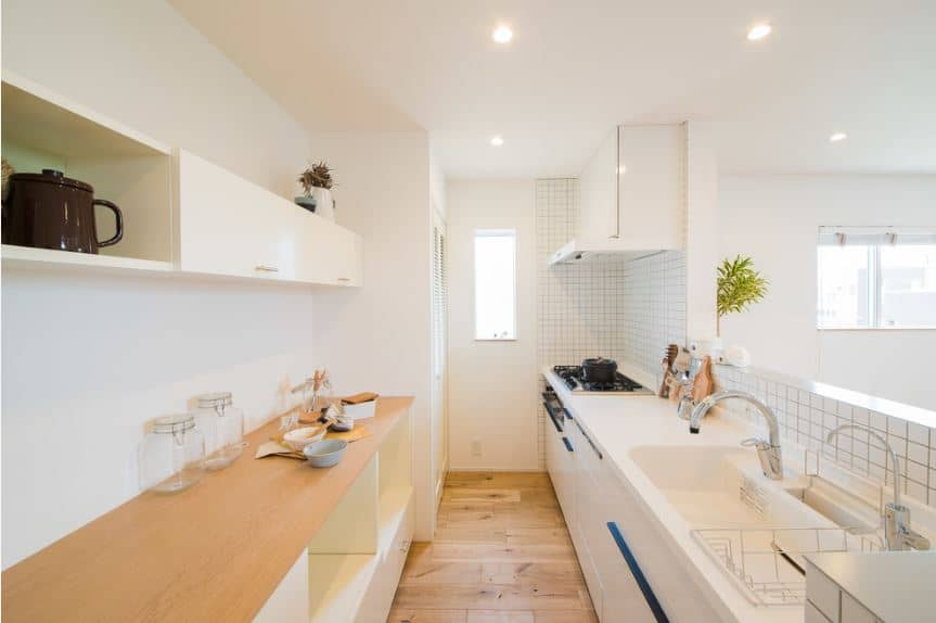 This hallway-like Scandinavian-Style kitchen has two peninsulas against the white walls across from each other. One has a wooden countertop and the other on has a white countertop that houses the sink and cooking area.