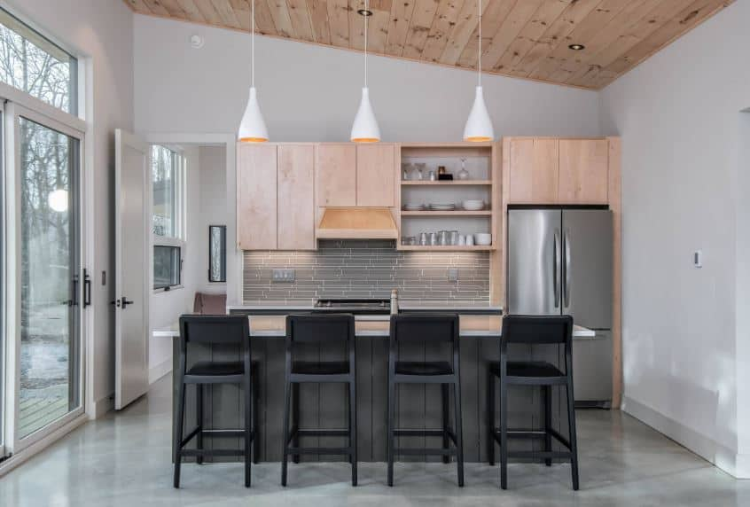This Scandinavian-Style kitchen has a shed wooden ceiling that supports three white pendant lights that hangs over the kitchen island. This kitchen island has a dark wooden body that pairs well with the dark stools. Against the wall is the cooking area that has hanging wooden cabinets and shelves.