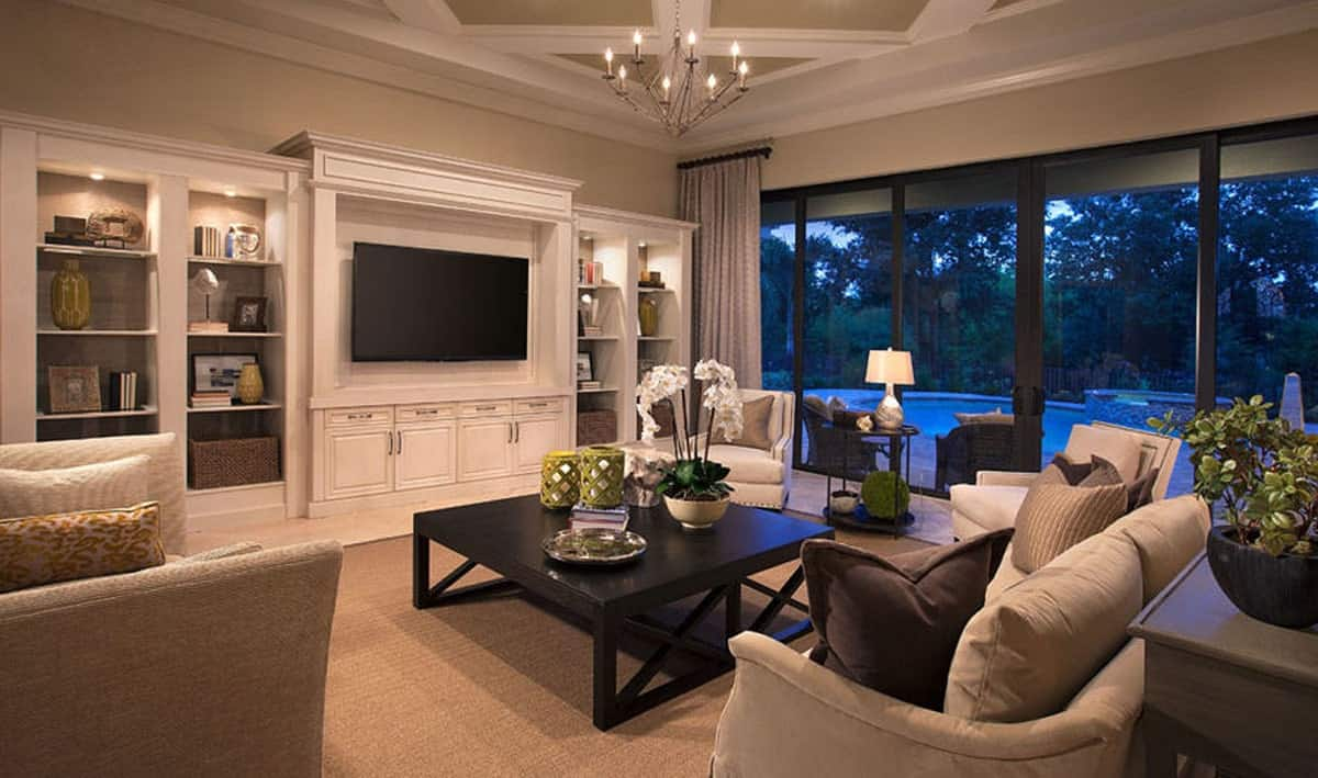 This charming living room has a coffered ceiling that hangs a small chandelier over the large dark wooden coffee table. This contrasts the large white structure on the wall that houses the TV along cabinets and shelves.