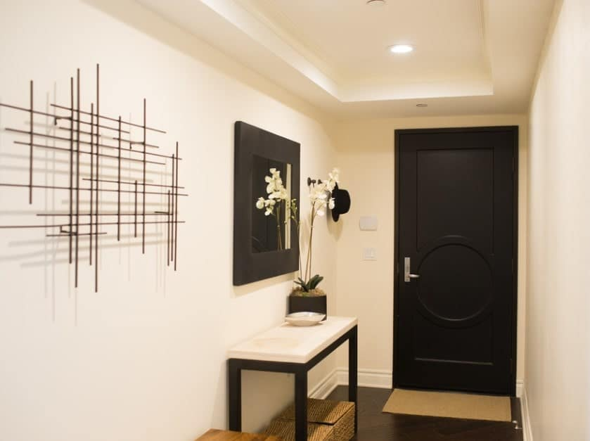 This simple and small foyer has a beautiful dark wooden main door with simple carved designs on it and a silver door handle. This matches well with the frame of the wall-mounted mirror that stands out against the bright beige walls and tray ceiling.