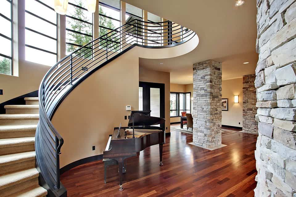 This elegant foyer has a wide hardwood flooring complemented by the grand piano by the curved stairs and the large stone pillar.