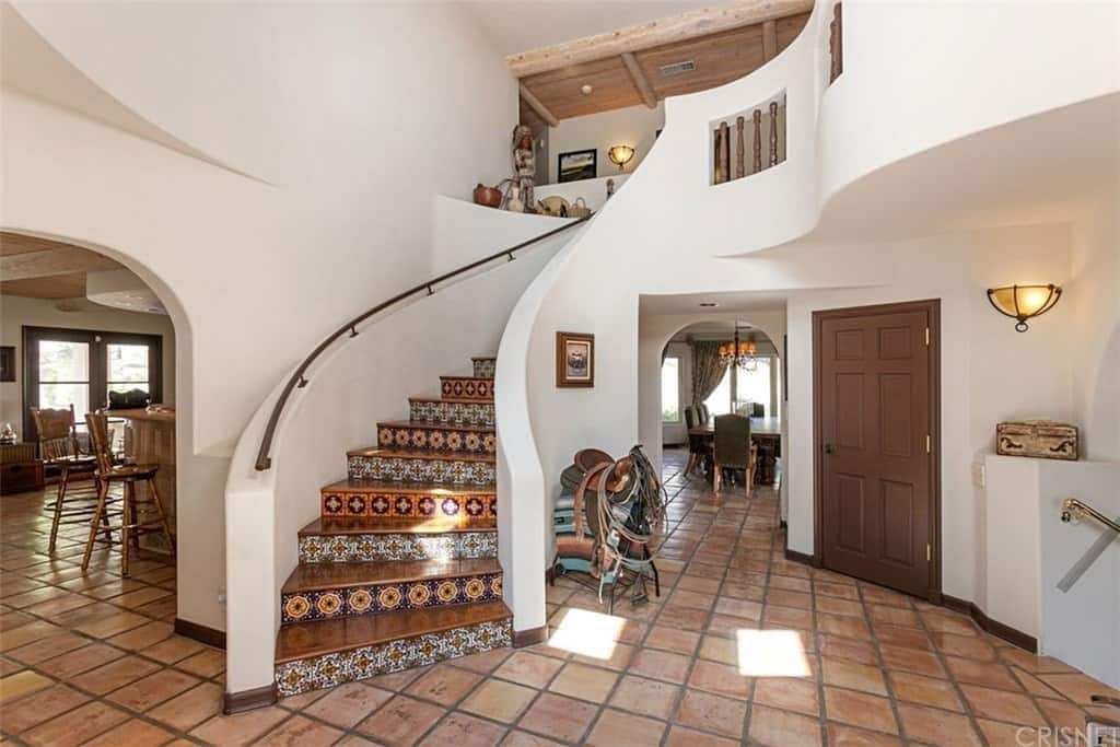 This charming Southwestern-style foyer has terracotta flooring tiles that sets an earthy contrast to the white walls and the white siding of the staircase. This bright sides of the staircase makes the patterned tiles of the ledges stand out along with the shiny brown steps.