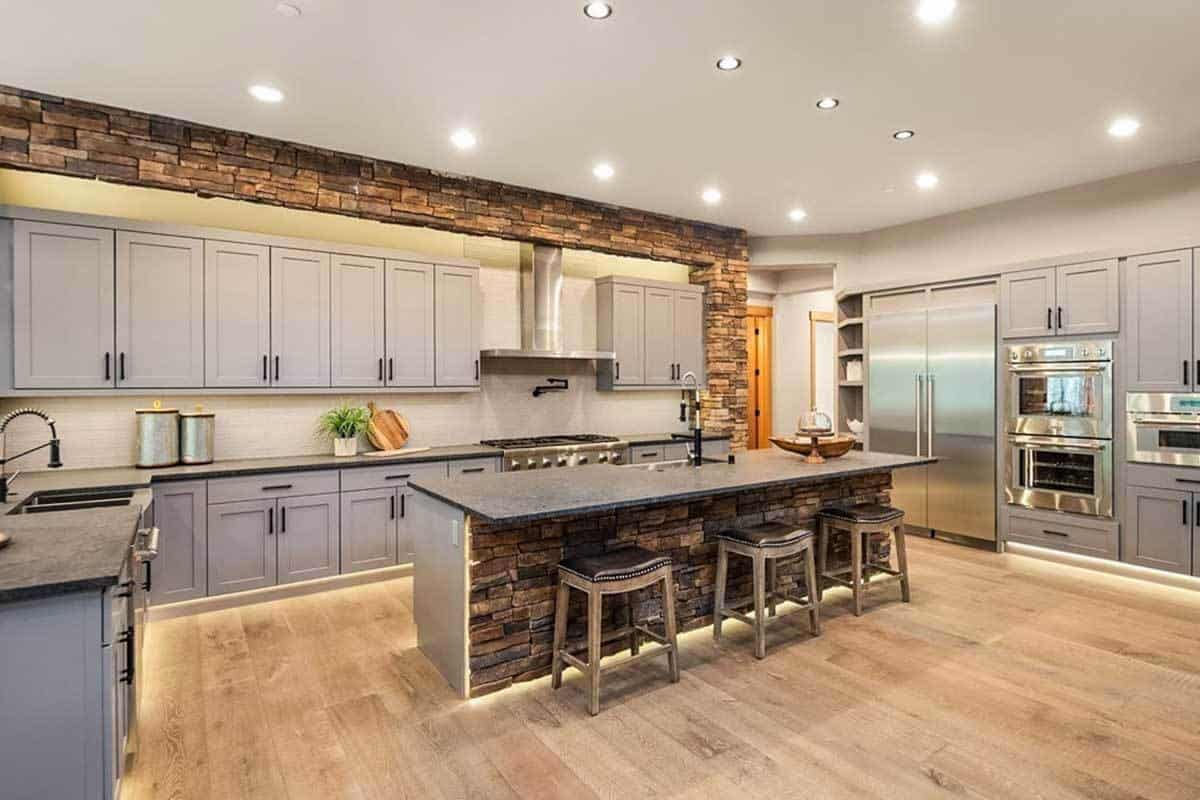 The lovely light gray cabinetry lining the walls of this kitchen is a nice match for the stainless steel appliances. These are then complemented by the bright ceiling with recessed lights and the spacious hardwood flooring with a large light gray kitchen island in the middle.