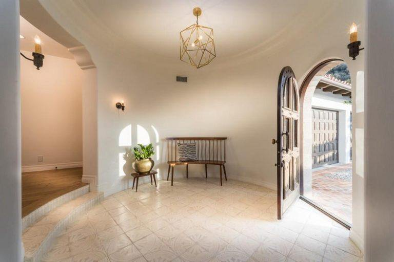 This Spanish-style foyer has curved light gray walls that follows the round ceiling that hangs a gold modern geometric pendant light over the bright pink patterned flooring tiles. This makes the wooden bench stand out as well as the wooden main door.