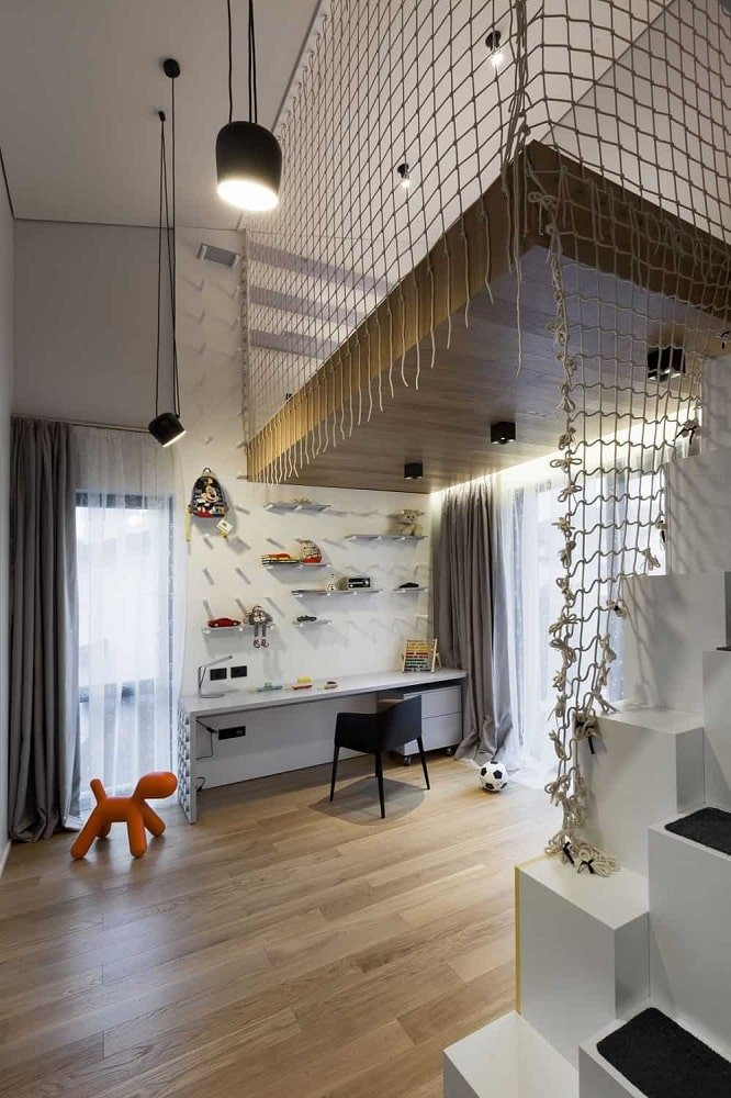 This is a boys bedroom that is designed to look like a playroom with a loft bed surrounded by rope for safety and underneath it is the study area with a built-in desk.
