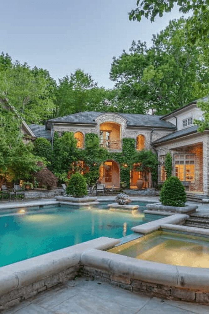 A backyard swimming pool integrated with a hot tub. The pool occupies most of the backyard space. It complements well with the stone house and surrounding greenery.