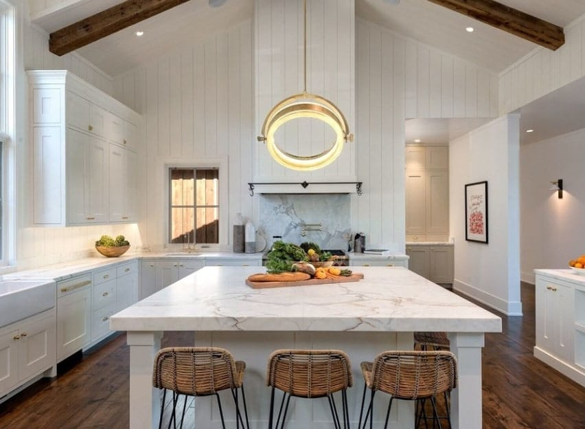 This kitchen featuring a high ceiling also boasts hardwood flooring and marble countertops on both kitchen counters and center island. The pendant ceiling light looks absolutely charming.