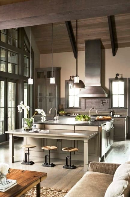 This kitchen boasts a large center island with a built-in breakfast bar lighted by pendant lights set on the high ceiling.