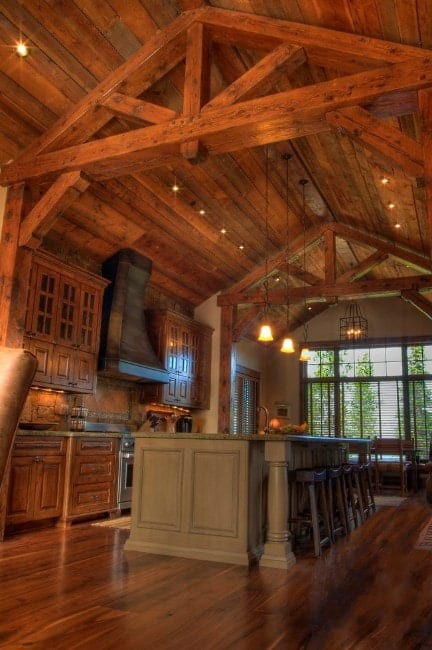 Rustic kitchen style with a high vaulted ceiling lighted by recessed and pendant lights. The center island looks stylish and it also provides space for a breakfast bar.