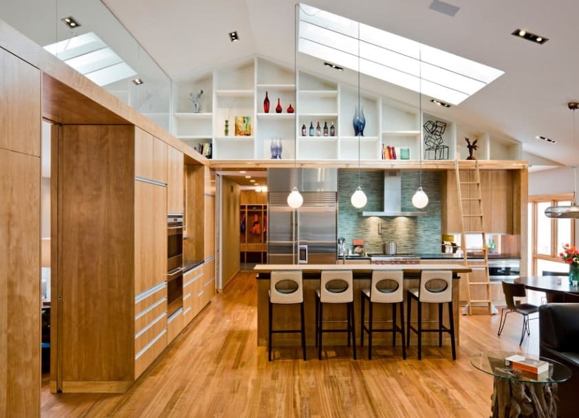 Large kitchen with walnut finished cabinetry matching the hardwood flooring. The high ceiling with skylight looks stunning.