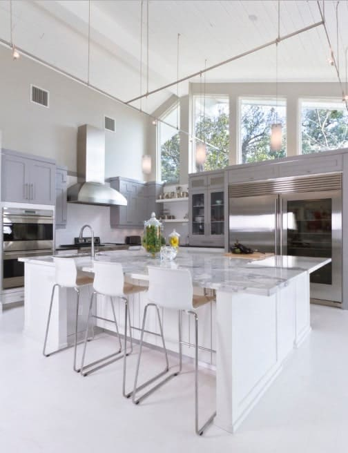 The high ceiling of this home is just jaw-dropping. The kitchen provides a large center island with a smooth marble countertop.