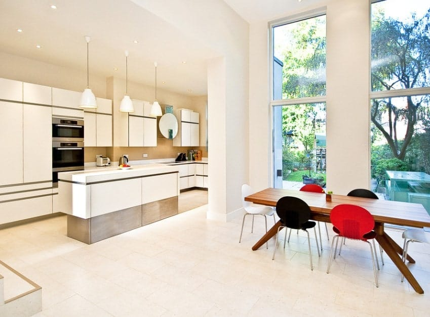 This kitchen features white cabinetry and kitchen counters along with a stylish center island lighted by pendant lights.