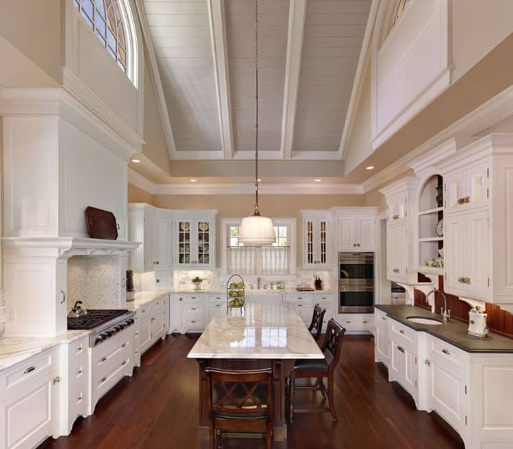 This elegant kitchen with marble countertops on both kitchen counters and the center island boasts high ceiling and hardwood flooring.