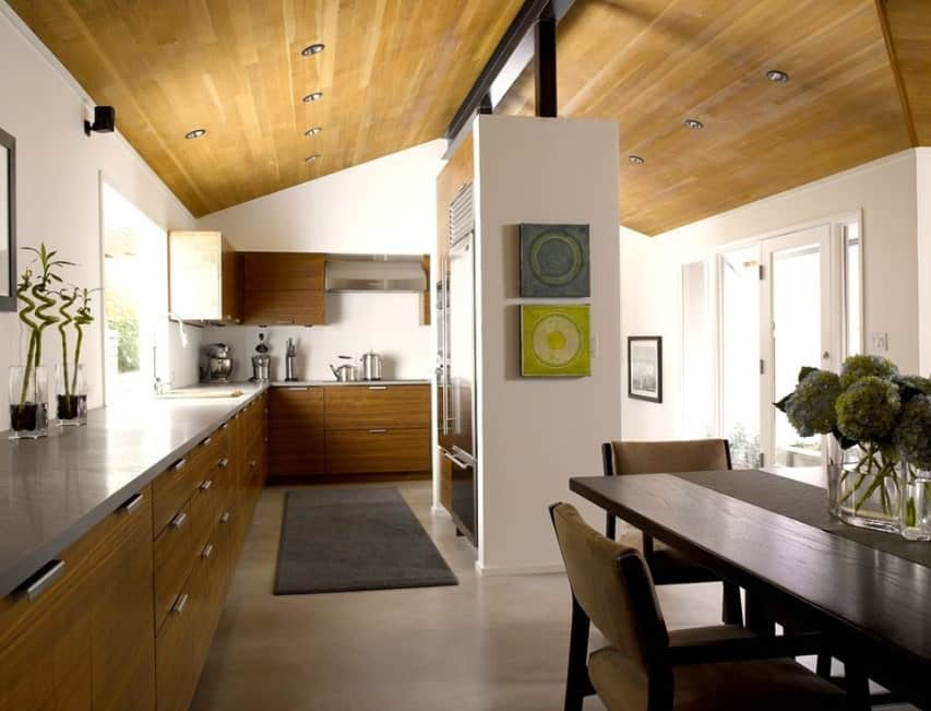 This kitchen boasts high vaulted ceiling along with an L-shape kitchen counter with smooth gray countertops.