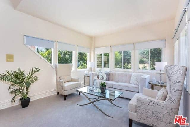 This is a simple traditional living room with a white ceiling and white walls housing a row of wrap-around windows. These are contrasted by the light gray carpeted flooring that makes the sofa set and glass coffee table stand out.