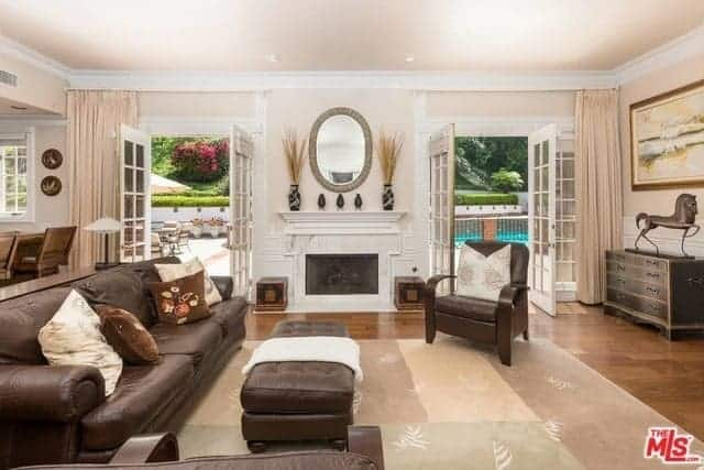 The white-matled fireplace is flanked by two French glass doors that bring brightness to the brown leather sofa set that matches the hardwood flooring.