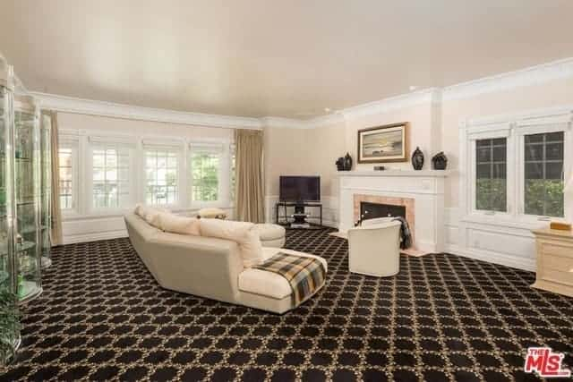 This simple living room is given a complex background of a dark patterned carpeted flooring that provide contrast to the beige walls, ceiling and leather sofa facing the fireplace with white mantle.