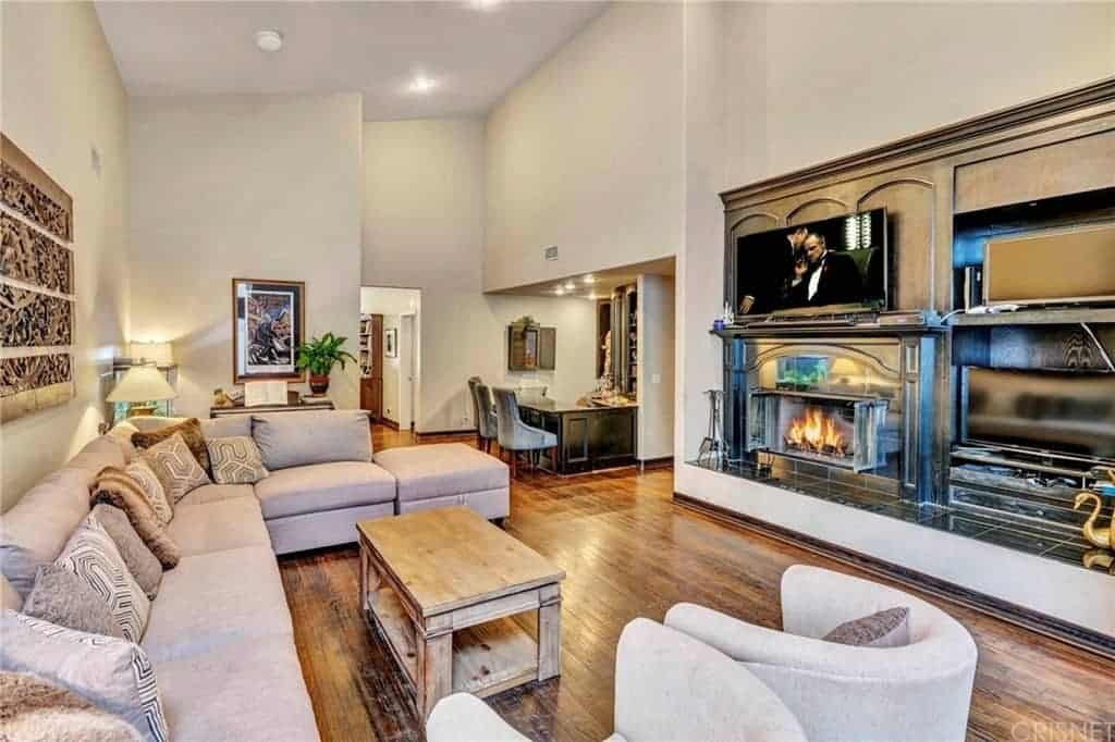 The hardwood flooring is well paired with the wooden coffee table surrounded by an L-shaped sofa facing the fireplace housed in a wooden structure where the TV is mounted.