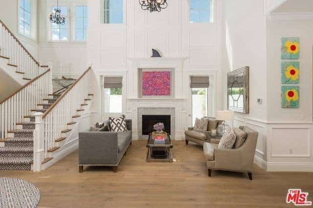 This high-ceilinged living room beside the stairs has high white walls with elegant finish. There are windows to maximize the vertical space as well as a dark iron chandelier over the comfortable sofas that suit the hardwood flooring.