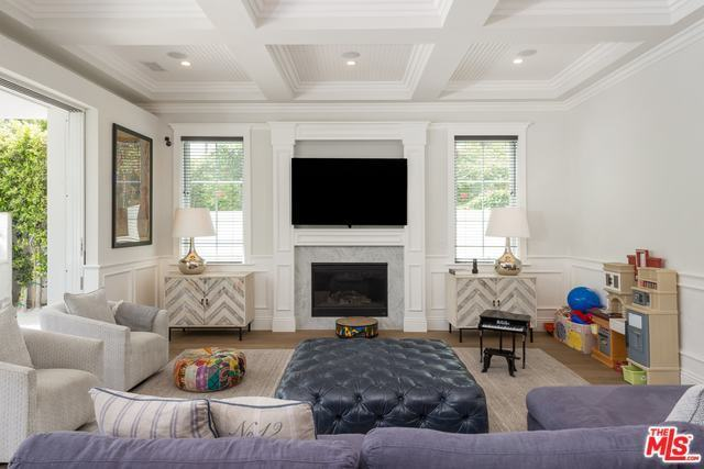 The fireplace has a white mantle with the TV mounted above it. This aesthetic is mirrored by the white coffered ceiling that blend with the white walls contrasted by the sofas and hardwood flooring.
