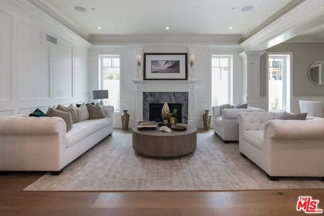 The white tray ceiling matches with the white mantle of the fireplace that faces a round brown coffee table that contrasts the light gray area rug blending with the white sofa set.