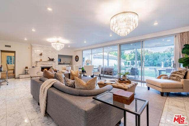 This is a great room with a huge glass wall that gives this living room an airy and spacious aura. this is augmented by the crystal semi-flush lights on the white ceiling that contrast the sofas.