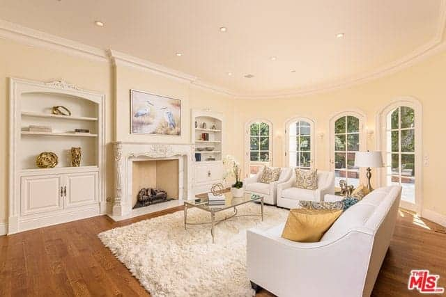 There is a row of four arched French glass doors on the beige wall that match with the beige ceiling and accented by the fireplace and the two built-in cabinets flanking it.