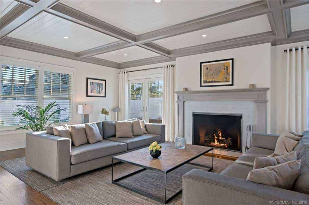 The ceiling has light gray coffers that match the mantle of the fireplace that warms up the gray sofas and gray area rug over the hardwood flooring.