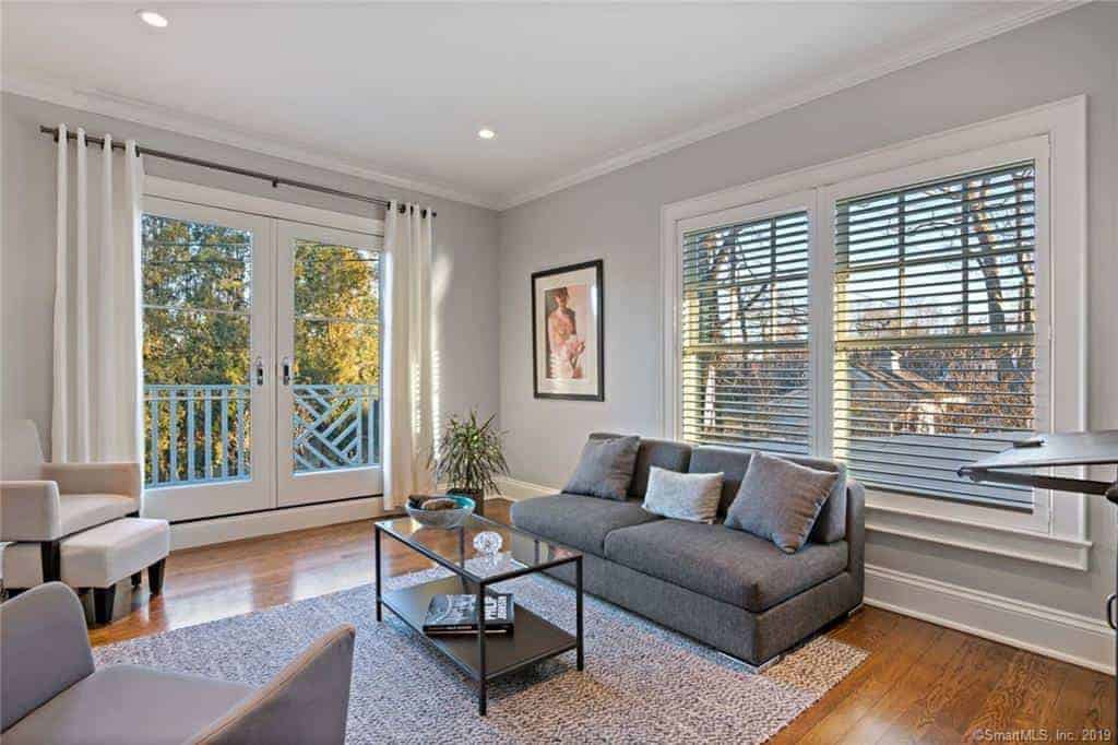 The shuttered windows provide natural lighting for the gray sofa that complements the light gray walls that is adorned with a wall-mounted painting beside the glass doors.