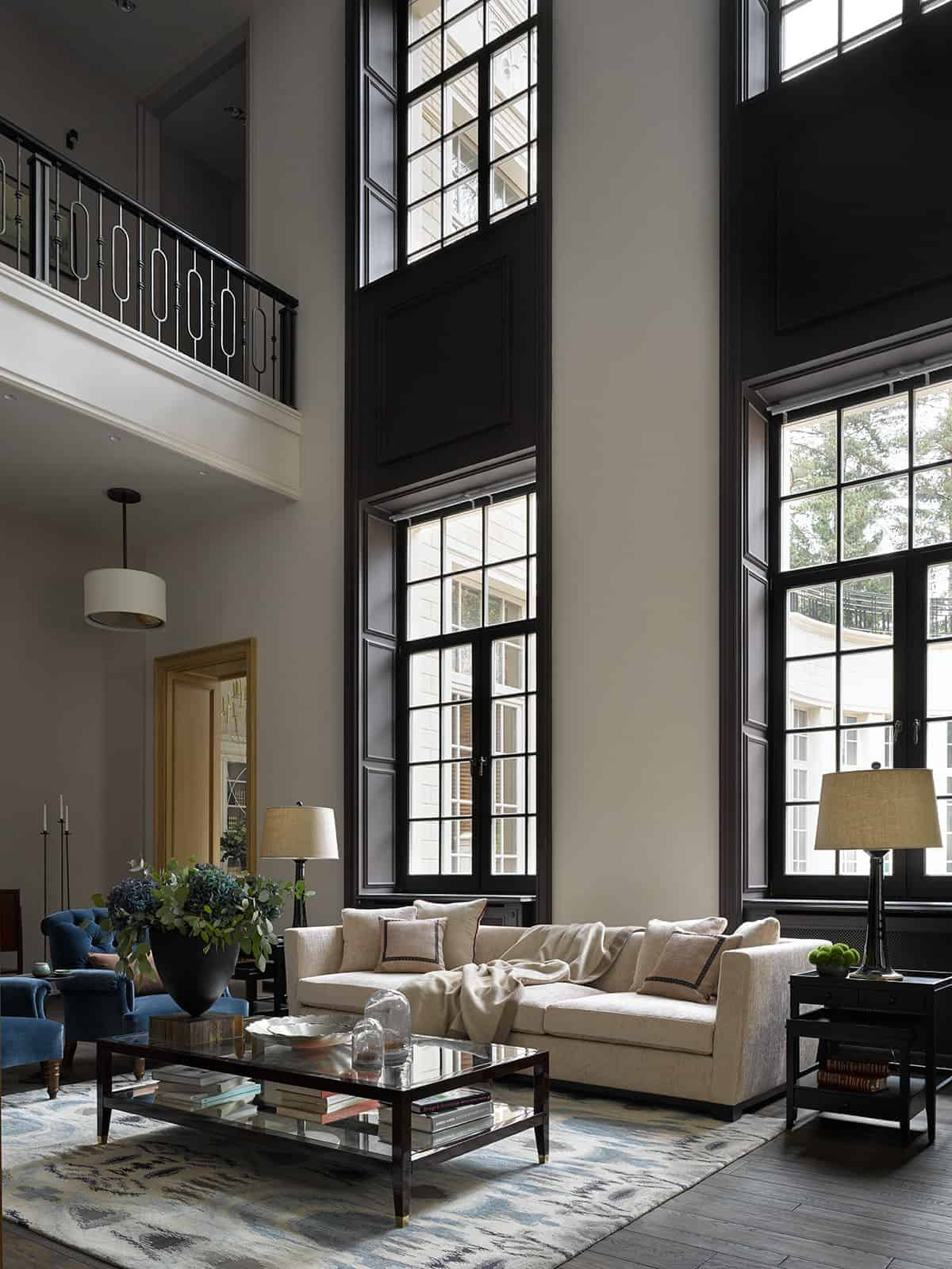 The beige sofa is illuminated by the tall windows that have a dark wooden finish and frame that match the dark side tables and coffee table over the light-hued area rug.